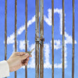 Hand hold key unlocking locked door with cloud house in blue sky — Stock Photo