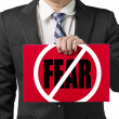 "Stock Photo: Businessmuse one hand to hold red board with ""No Fear"" conc"