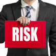 "Businessman use one hand to hold a red board with word ""risk"" cl — Lizenzfreies Foto"