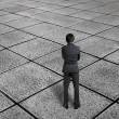 Rear view businessman thinking and standing on endless tiled flo — Stock Photo