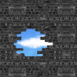 Broken bricks wall with a big hole and cloud, blue sky outside — Stock Photo