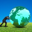Businessman rolling large green ball with global map on it isola — Stock Photo