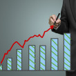 Stock Photo: Businessman drawing growth red arrow and chart