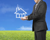 Palm opening businessman with cloud shape house in green meadow — Stock Photo