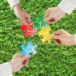Hands hold puzzles with recycle symbol in fresh meadow backgroun — Stok fotoğraf