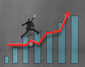 Businessman running and jumping on growth red arrow with chart — Stock Photo