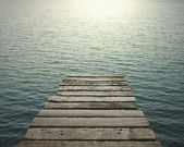 Old wooden pier to the sea with sunlight — Stockfoto