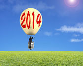 Man taking lamp balloon floating over meadow and looking at — Foto Stock