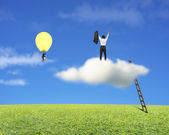 Businessman standing on cloud, another in lamp balloon — Stock Photo