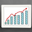 Stock Photo: Growth red arrow and chart on tablet with concrete wall