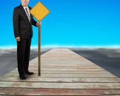 Businessman hold yellow board standing on wooden way — Stock Photo