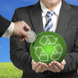 Inserting coin into ball with recycling symbol with nature backg — Stock Photo