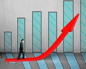 Businessman walking on growing red arrow with chart — Stock Photo