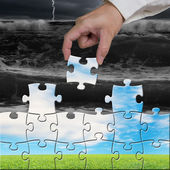 Hand holding puzzles to assembly for changing view — Stock Photo