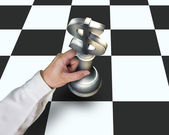 Hand holding USD symbol piece playing Chess on table — Stock Photo