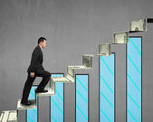 Businessman walking on money stairs with chart — Stock Photo