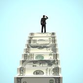 Businessman gazing on top of money stairs  — Photo
