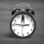 Standing on alarm clock hands — Stock Photo