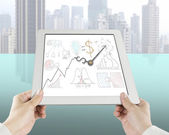 Holding tablet with business concept drawing and clock hands — Stock Photo