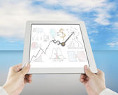 Hand holding tablet with business concept doodles and clock hand — Stock Photo