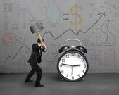 Businessman hitting clock with business doodles on wall — Stock Photo