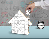 Finishing to assemble puzzles in house shape  — Stock Photo
