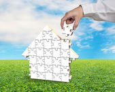 Assembling puzzles in house shape on sod — Stock Photo