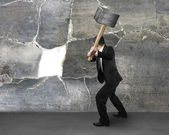 Businessman holding sedgehammer to crack wall — Stock Photo