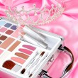 Makeup briefcase on pink satin and diadem - Stock Photo