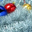 Three celebratory sparkling spheres and a tinsel — Stockfoto