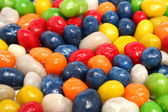 Horizontal background made of multi-coloured sweets with raisin — Stock Photo