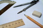 Compasses, pencil and rulers on squared paper — Stock Photo