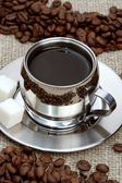 Cup of coffee with lump sugar and beans — Stock Photo