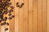 Grains of coffee on a wooden carpet — Stock Photo