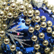 Blue glass sphere and celebratory beads on a white — Stock fotografie