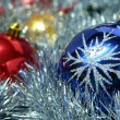 Three christmas glass spheres and a tinsel — Stok fotoğraf