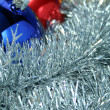 Three christmas sparkling spheres on a tinsel - Stock Photo