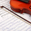 Violin with bow on music book — Stock Photo