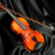 Violin and bow on black silk — Stock Photo