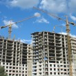 Two yellow tower cranes on a construction site — Stock Photo #14468643
