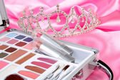 Makeup briefcase on pink satin and diadem — Stock Photo