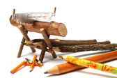 Pencils from natural wood of various type near to a saw — Foto Stock
