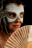 Young brunette with venetian mask and spanish fan — Stock Photo