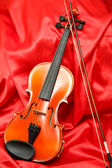 Violin and bow on red silk — Stock Photo