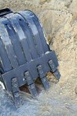 Black shovel bucket near to a heap of sand — Stock Photo