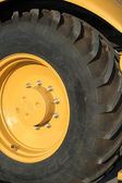Wheel of a new yellow building tractor — Stock Photo