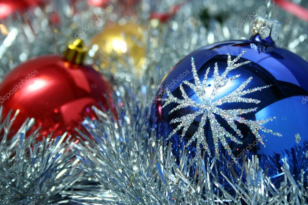 Three christmas glass spheres of dark blue, yellow and red color with a pattern on a background of a New Year's tinsel, (look similar images in my portfolio) — Stock Photo #14461515