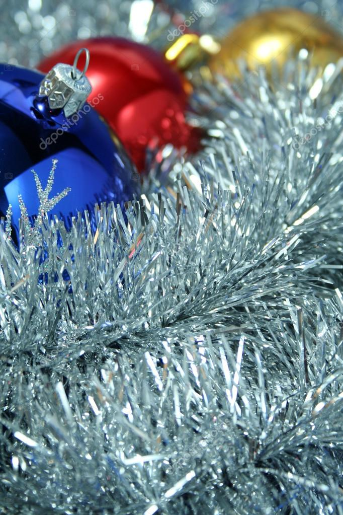 Three christmas sparkling spheres of dark blue, yellow and red color on a background of a silvery New Year's tinsel, (look similar images in my portfolio) — Stock Photo #14461551