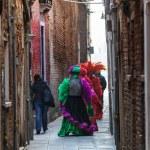 Venetian Costumes Walking on a Narrow Street in Venice — Stock Photo #13507815