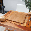 Empty Chinese go board and bowls on table in yard - Stock Photo